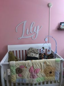 a white crib with a winnie the pooh blanket in a pink baby girl disney nursery with the name lily on the wall