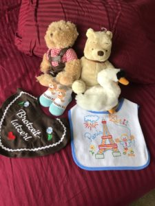 european souvenirs on a red background, including parisan bib, pooh bear stuffed animal, stuffed goose, and a small german stuffed bear
