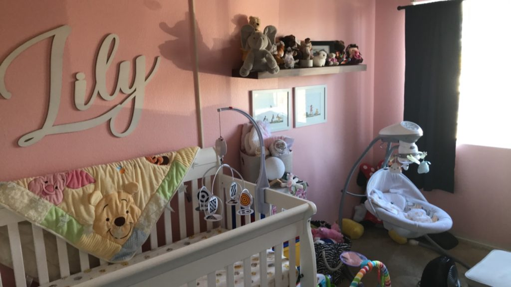 a pink winnie the pooh themed baby girl disney nursery with a baby swing, white crib, and lily on the wall