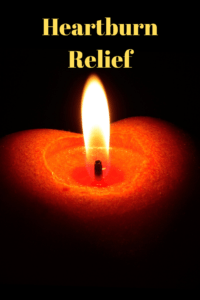 """a red burning heart-shaped candle in a black room with text """"heartburn relief"""""""