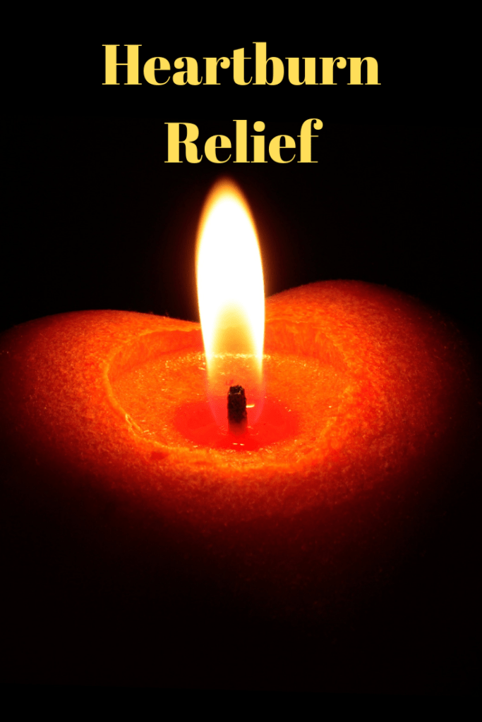"a red burning heart-shaped candle in a black room with text ""heartburn relief"""