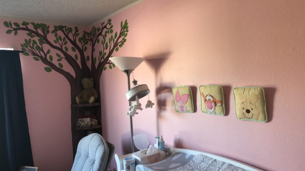 a painted tree mural in the corner of a baby girl pooh bear disney nursery with pooh bear characters on the wall over a changing table