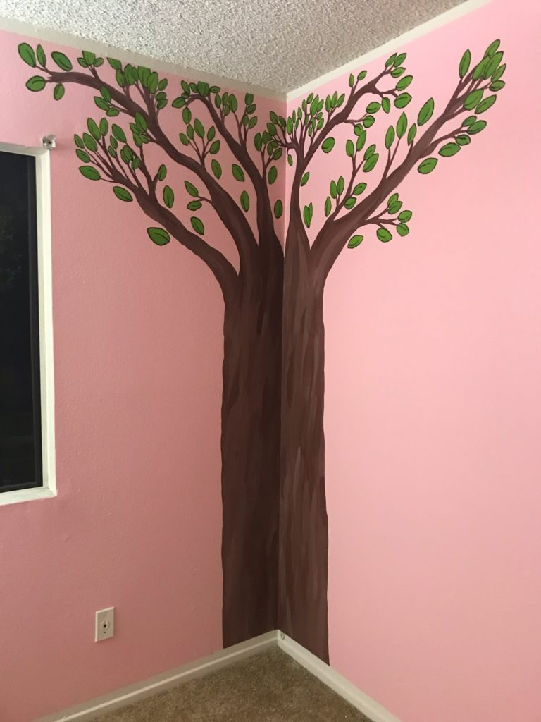 a painted tree mural on the wall of a pink baby girl nursery