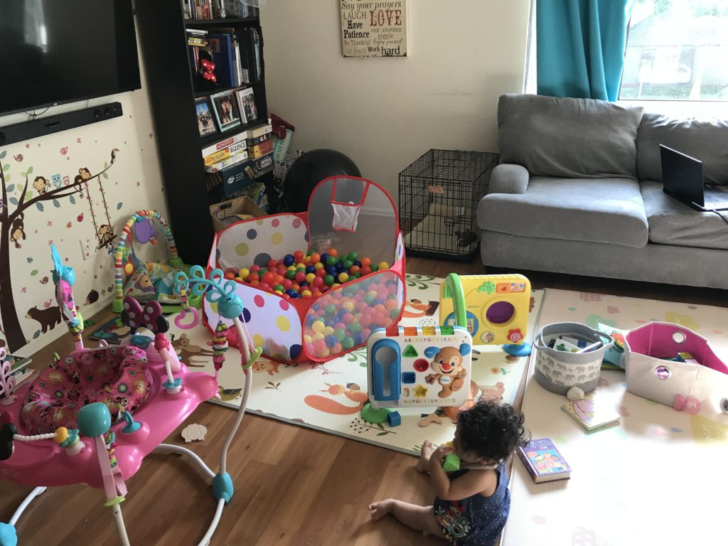 a baby sitting on a mat in the middle of toys messy fun living room
