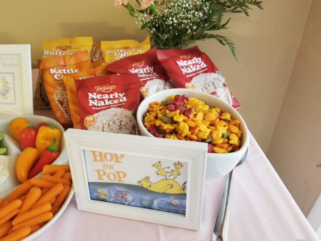 individual bags of popcorn and a bowl of goldfish saying 'hop on pop' and 'the rainbow fish' childrens book