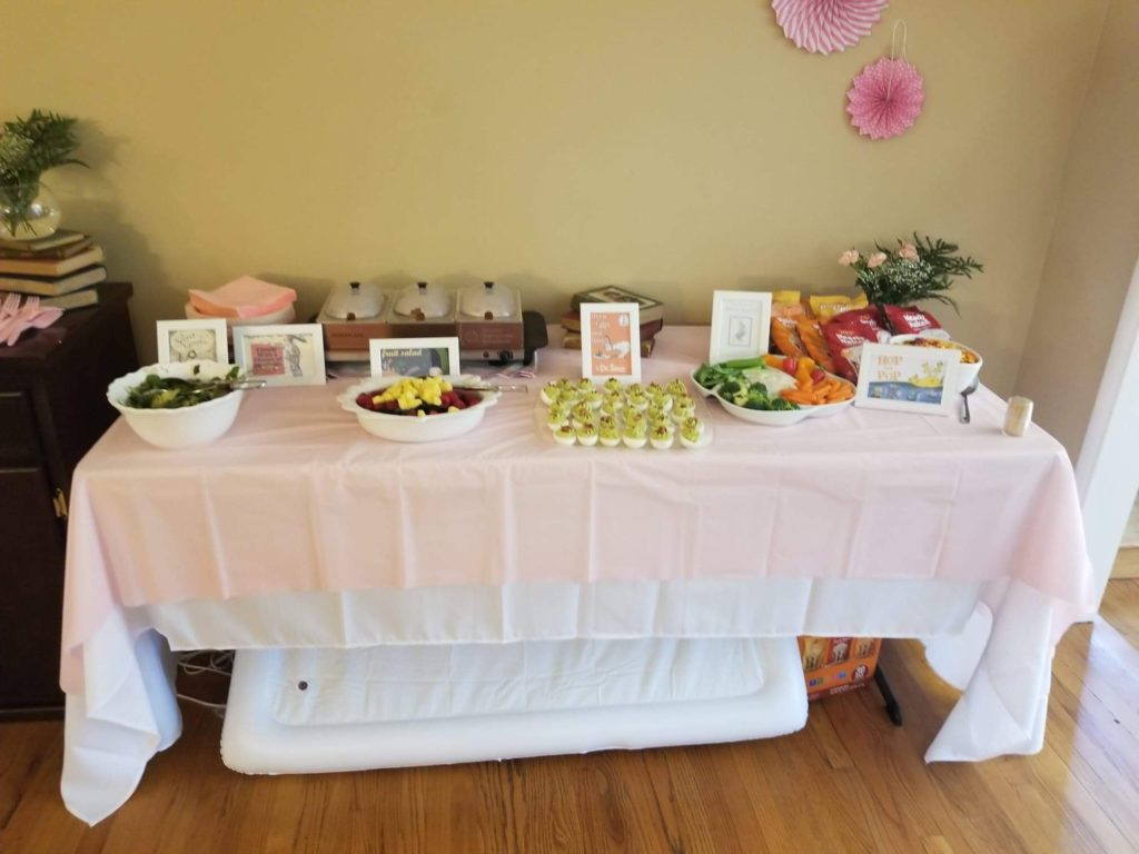 food table with childrens books themed food for a baby shower on it