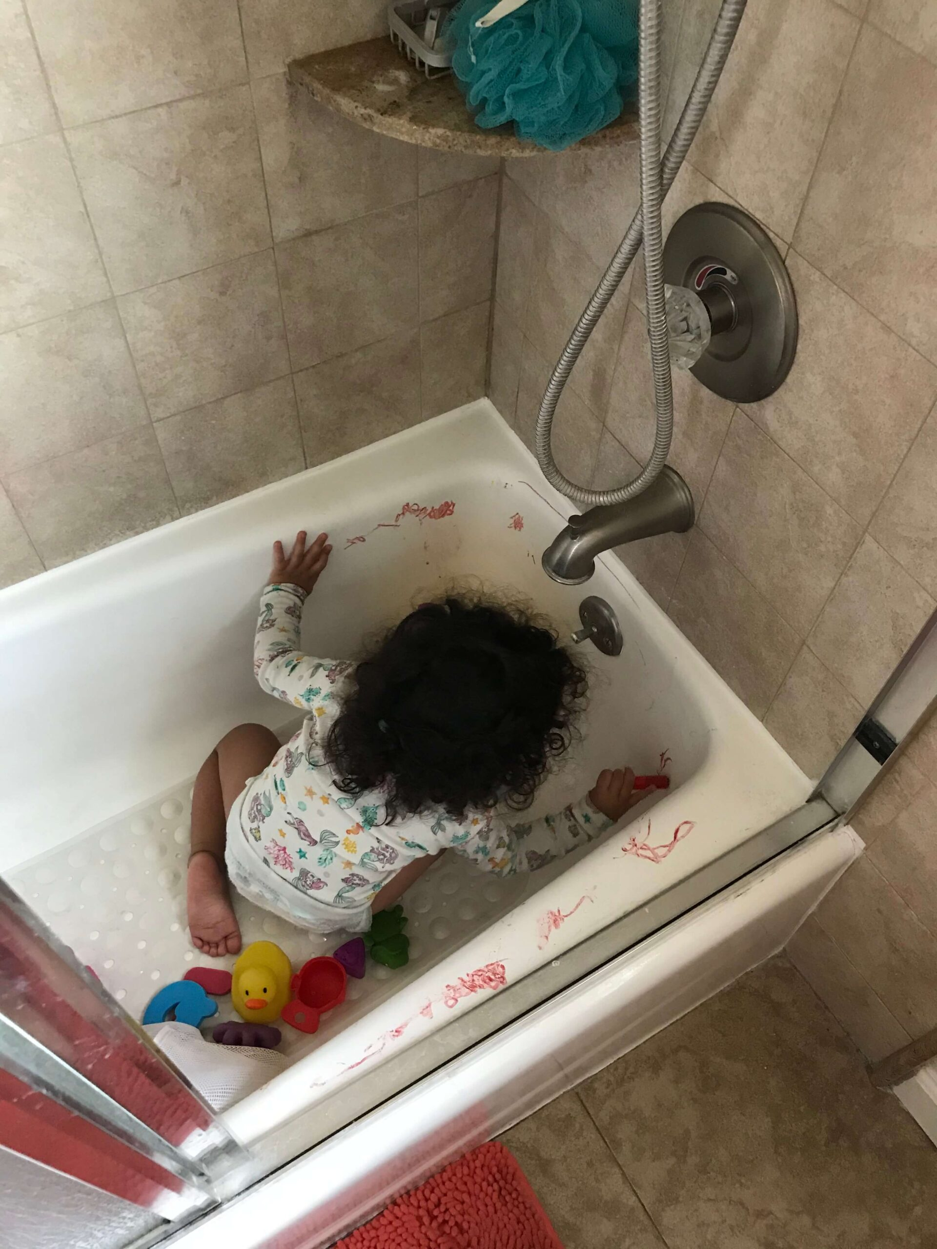 toddler coloring her bathtub with bath crayons