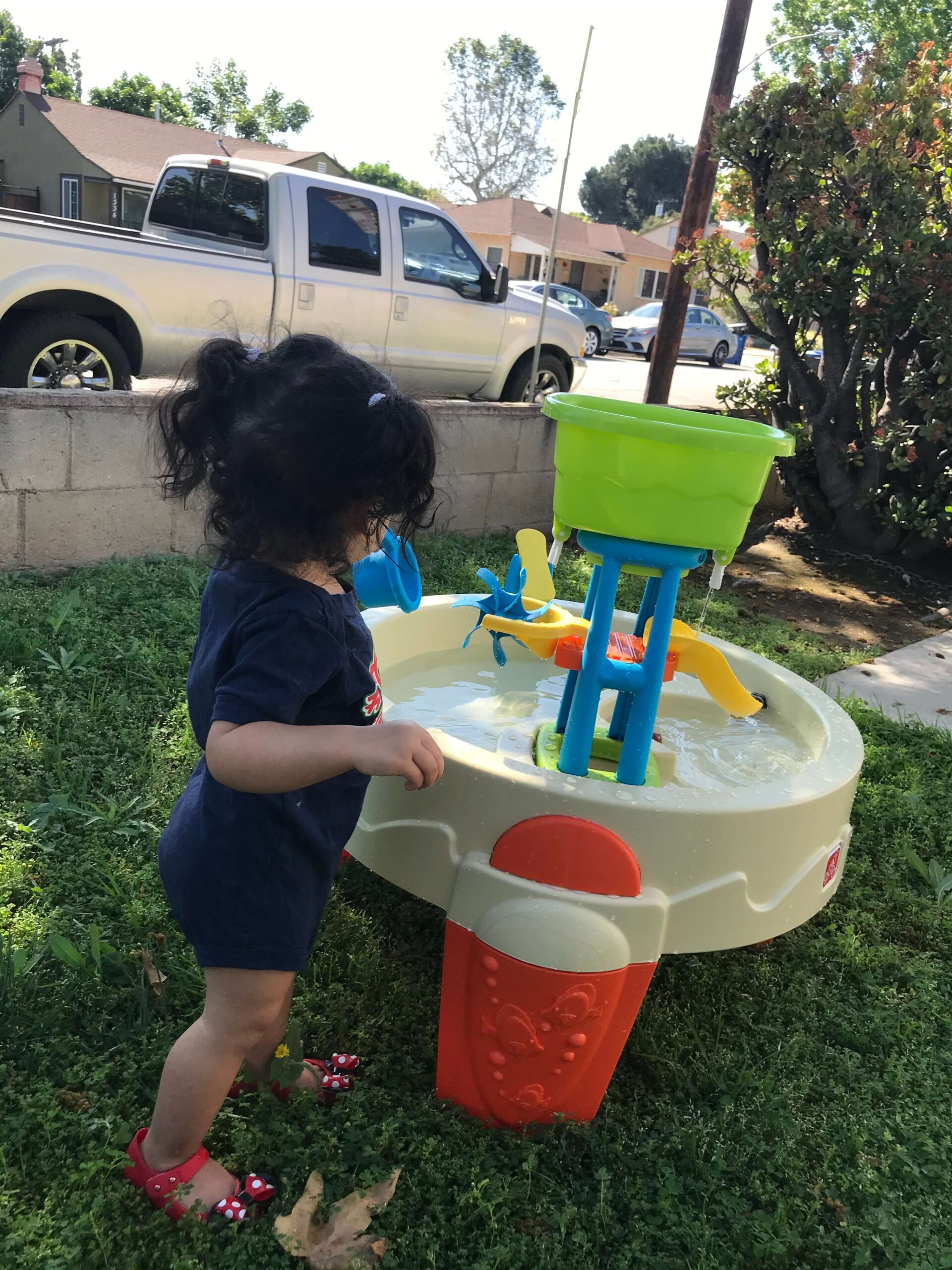 toddler playing with a water table outside