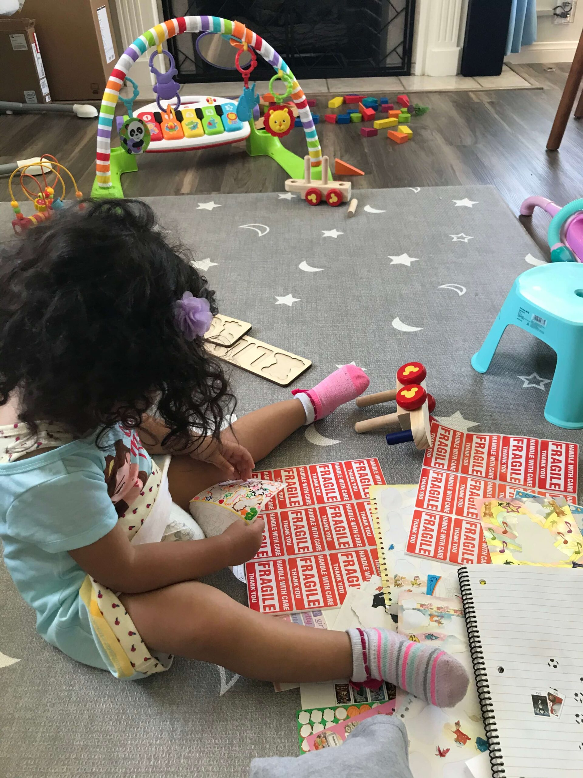 toddler with several sheets of stickers in front of her