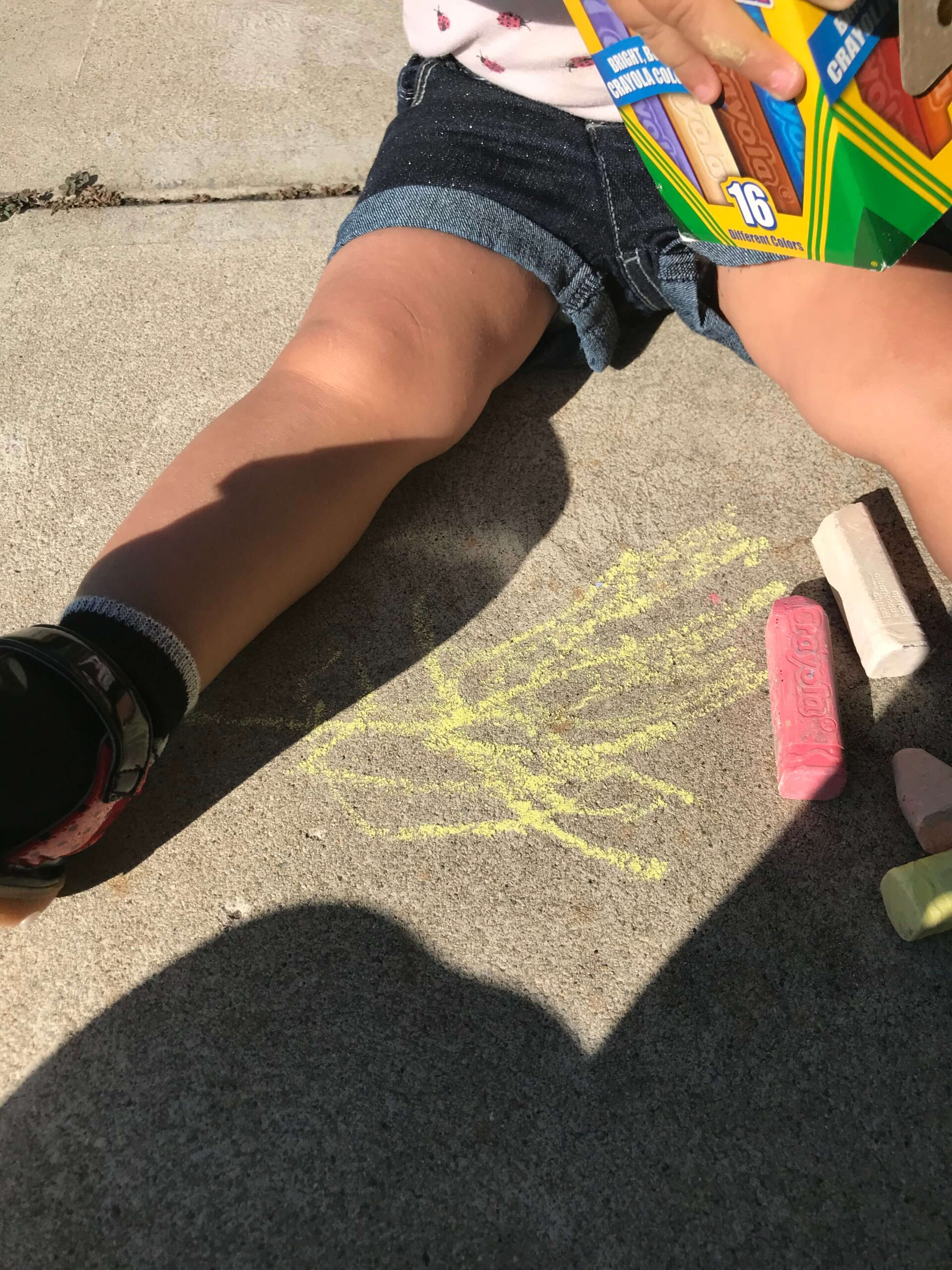 pieces of chalk with chalk drawing on sidewalk in between toddler legs