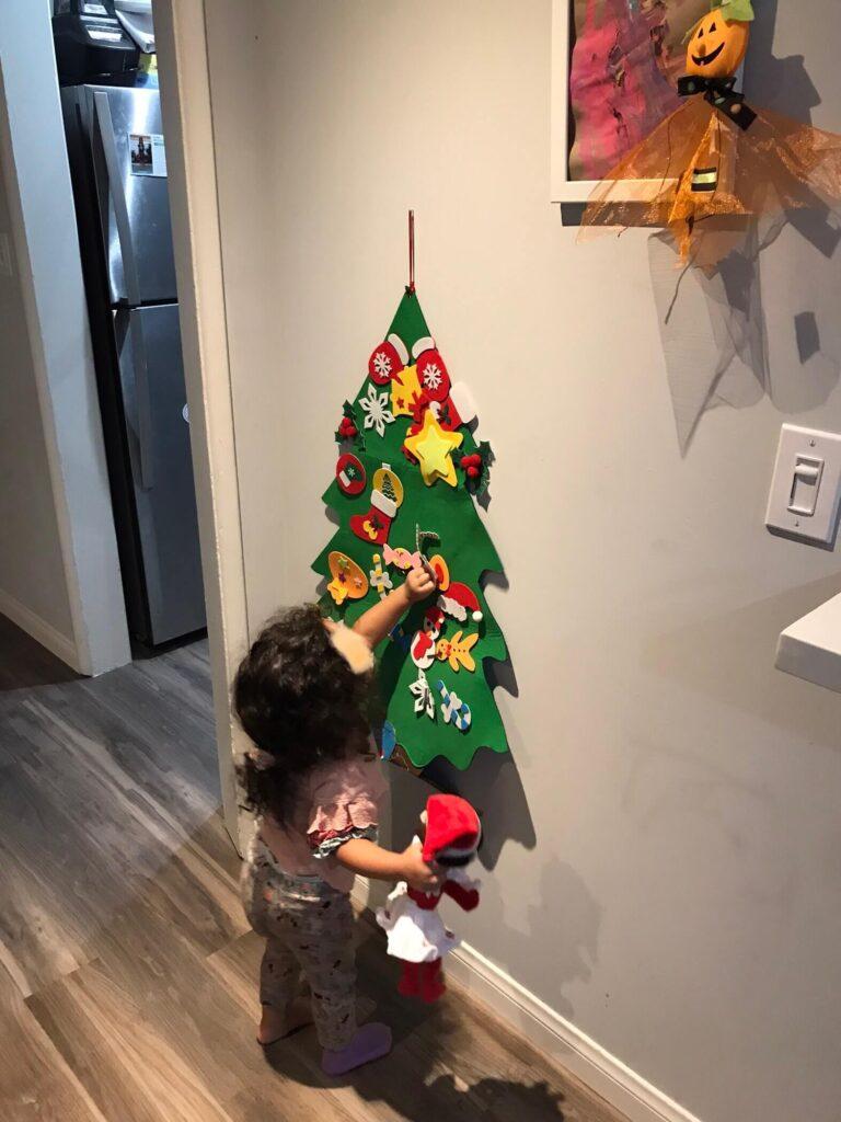 a toddler girl placing a felt ornament on a felt Christmas tree