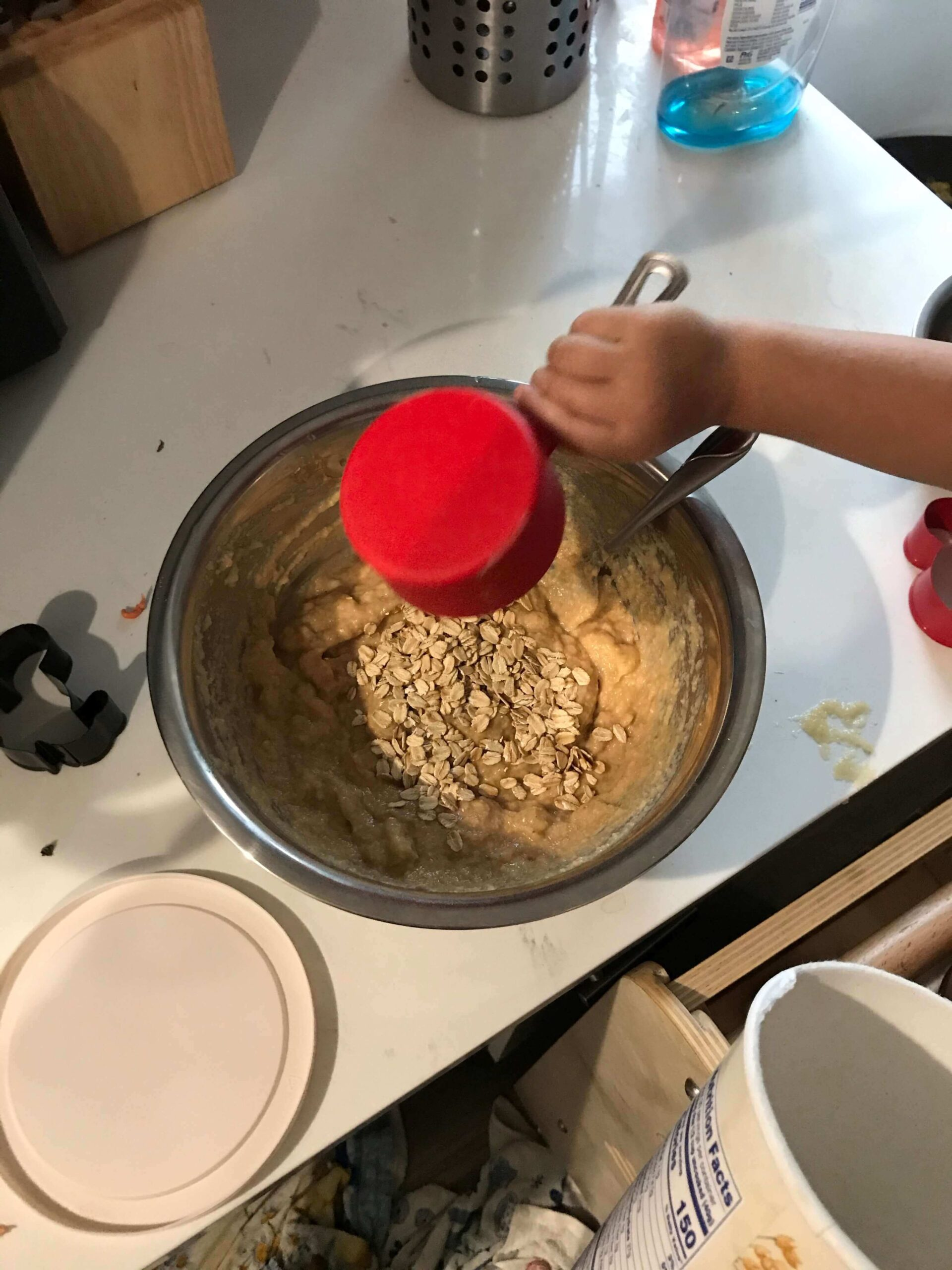 a little hand measuring ingredients into a mixing bowl to make cookies