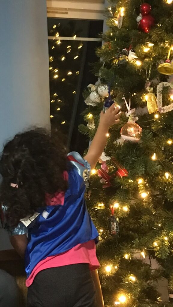 a toddler girl placing ornaments on a lit Christmas tree
