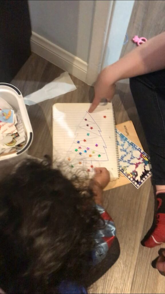 a toddler girl placing stickers on a drawn Christmas tree on paper