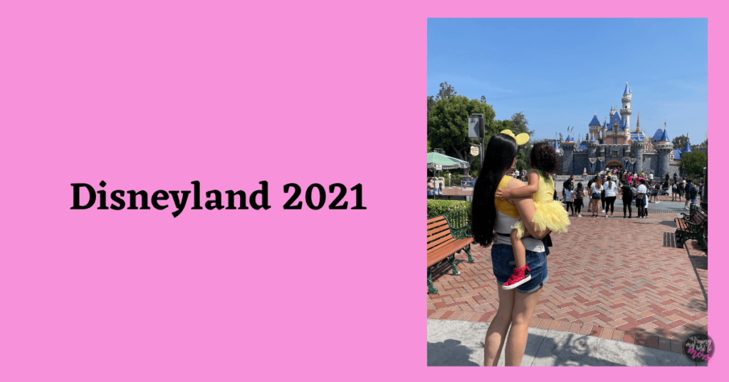 mom and toddler looking at sleeping beauty castle at disneyland with text disneyland 2021