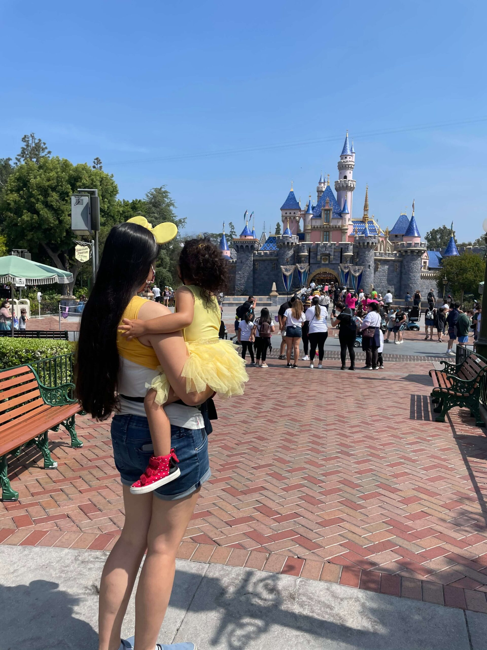 mom and toddler dressed as belle look at the sleeping beauty castle at disneyland