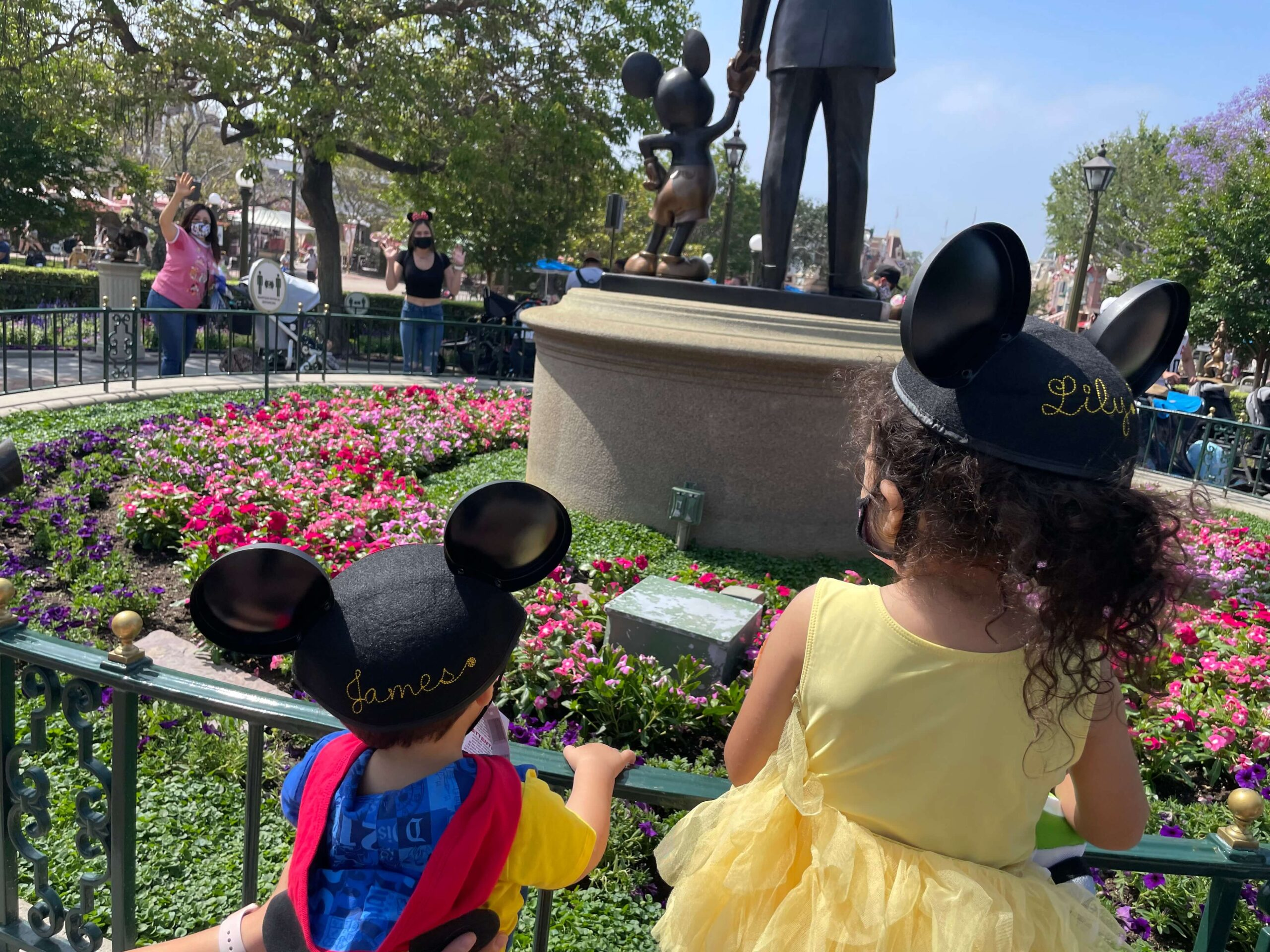 two toddlers with mickey ear hats in front of the statute of walt disney and mickey mouse at disneyland