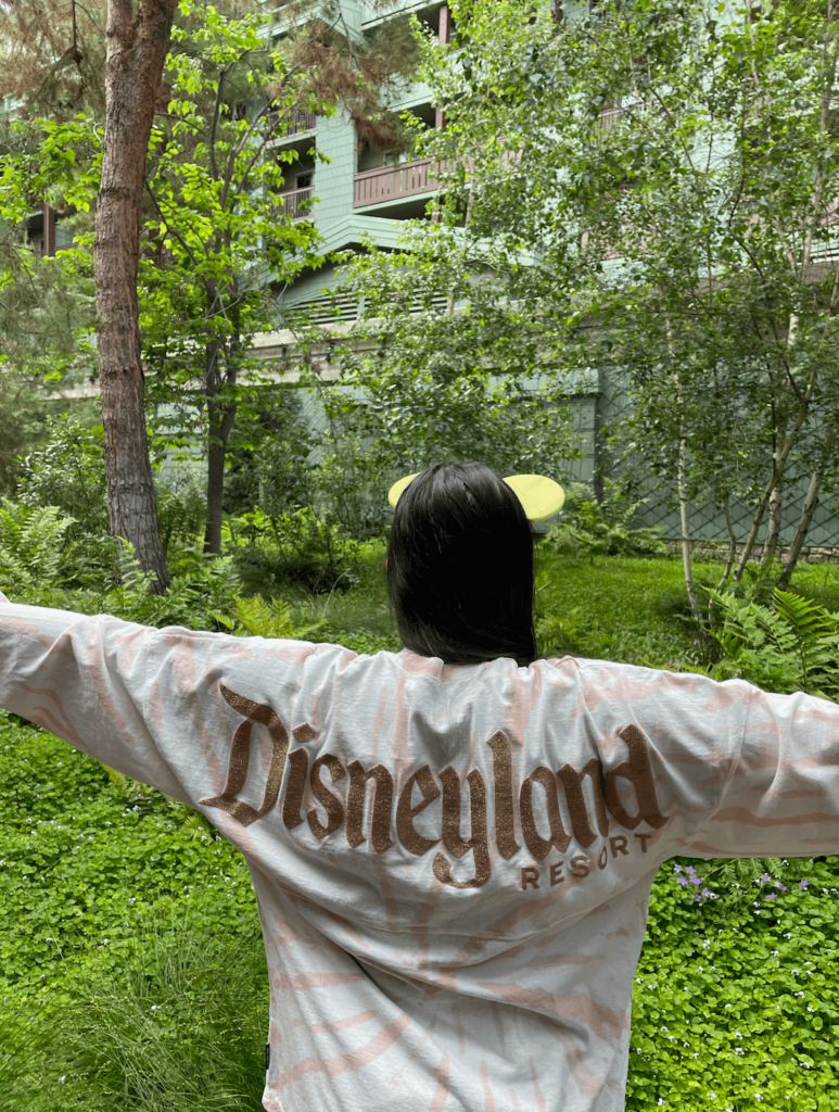 a woman wearing a disneyland resort spirit jersey facing the landscaping at the grand californian hotel
