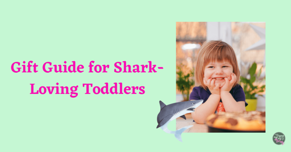toddler smiling with text gift guide for shark loving toddlers